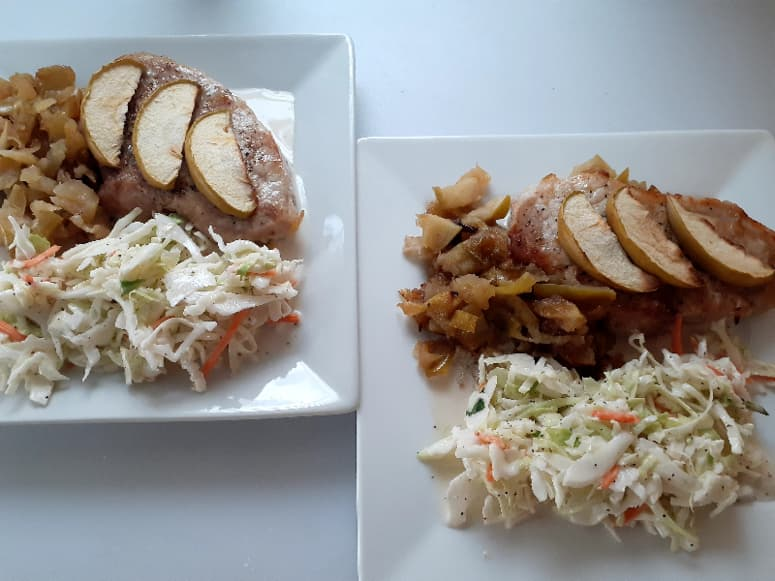 A closeup of plated applesauce pork chops and coleslaw on two white plates.