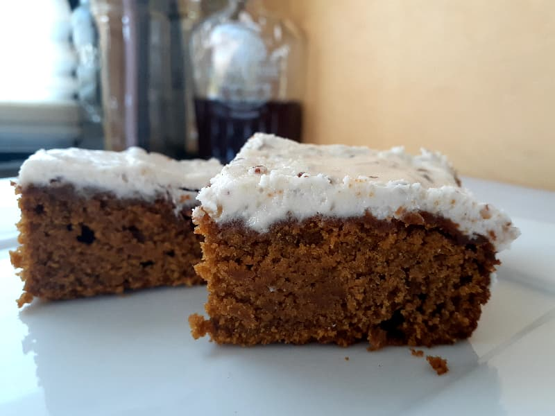 Closeup of two pumpkin bars on a white plate.