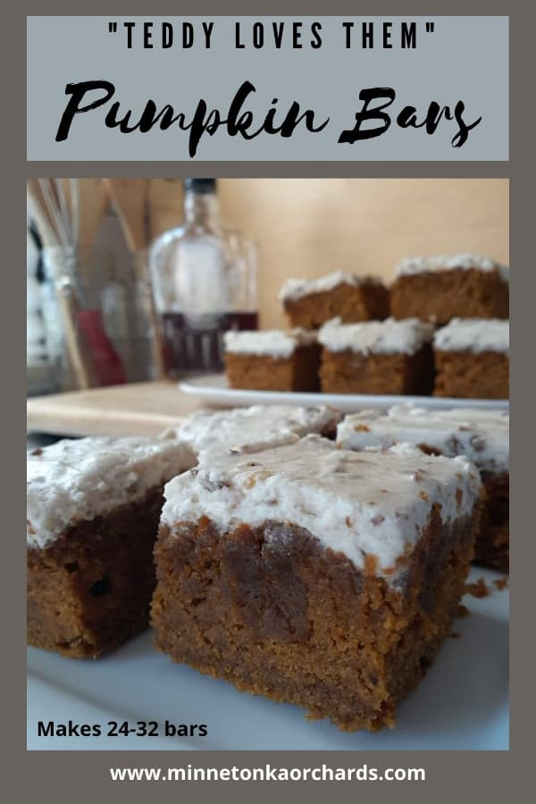 Pinterest image of a closeup of pumpkin bars on a white plate with more pumpkin bars stacked on a white plate, along with a bottle of maple syrup in the background.