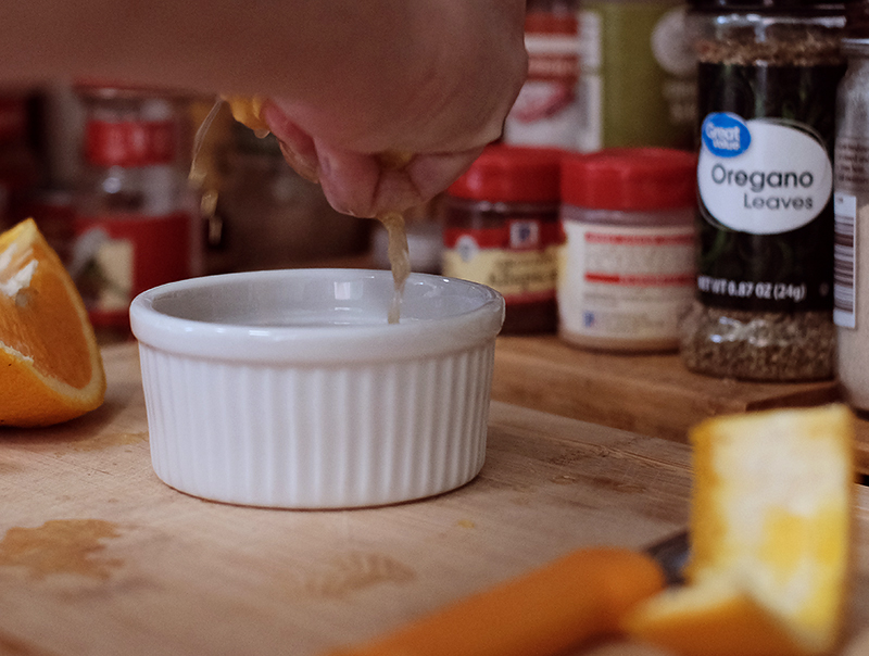 Closeup of hand squeezing an orange into a white ramekin with spice jars in the background.