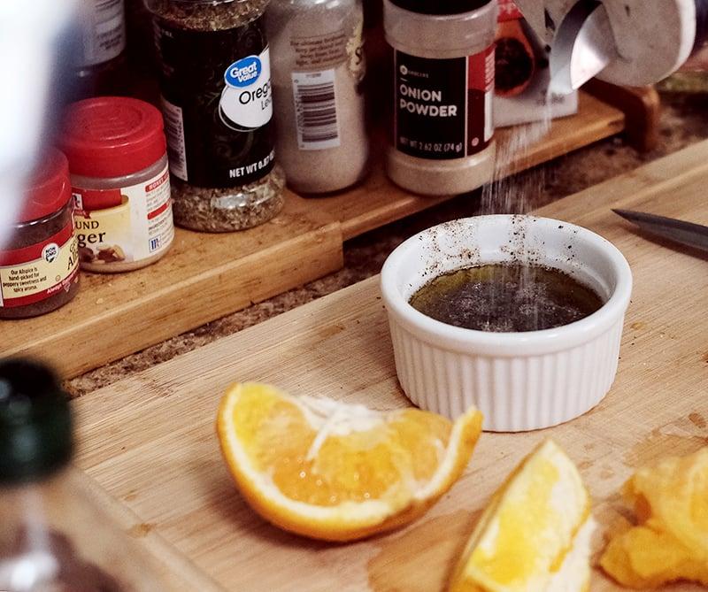 Closeup of ground black pepper being added to a ramekin of salad dressing .