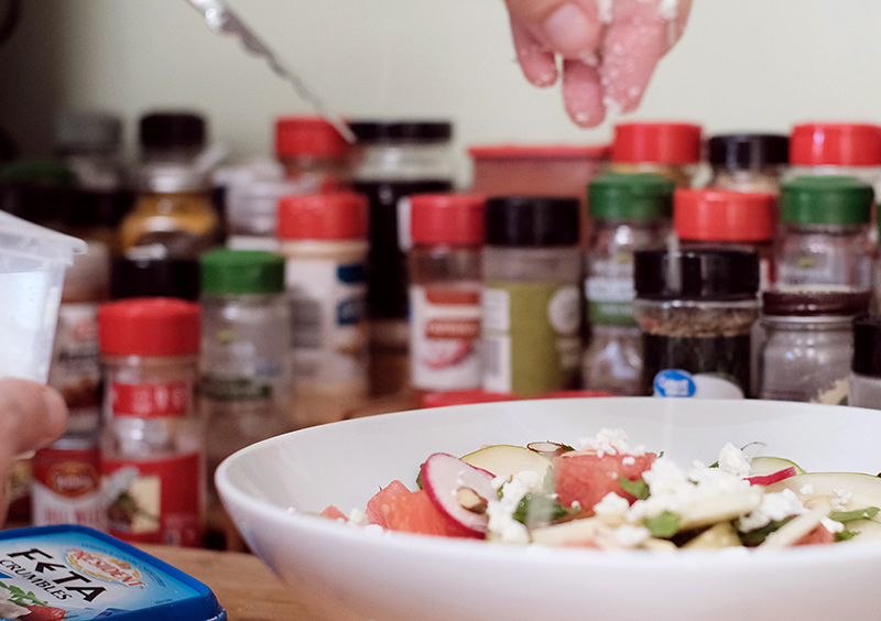 Closeup of hand sprinkling crumbled Feta cheese into watermelon, radish salad with jars of spices in the background.
