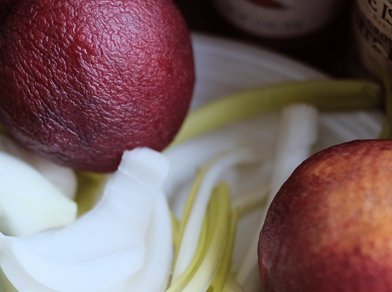 Closeup of green onions and nectarines in a white bowl.
