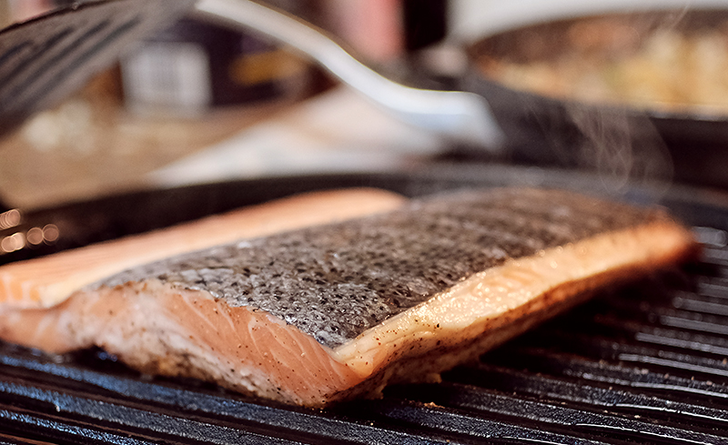 Salmon fillets, skin side up, on a grill pan