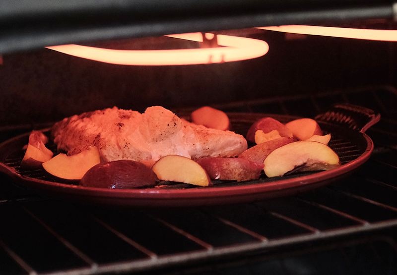 Grill pan of salmon and nectarines underneath an oven broiler