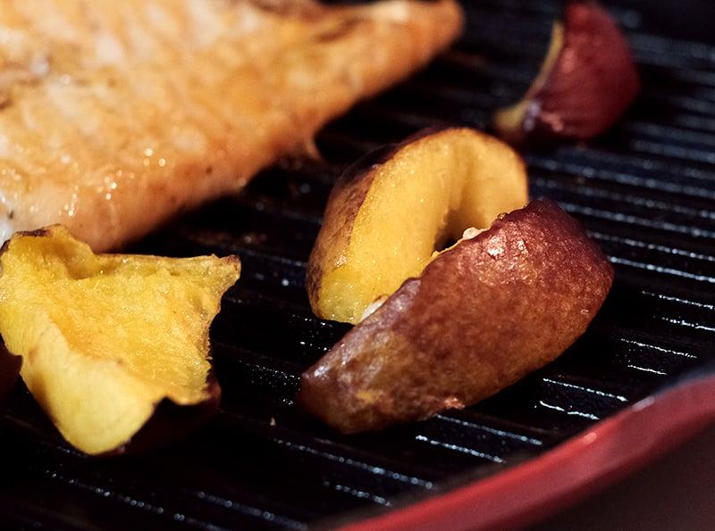 Nectarine slices on grill pan next to salmon fillet