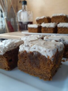 Closeup of Pumpkin Bars with Maple Frosting on white plates.
