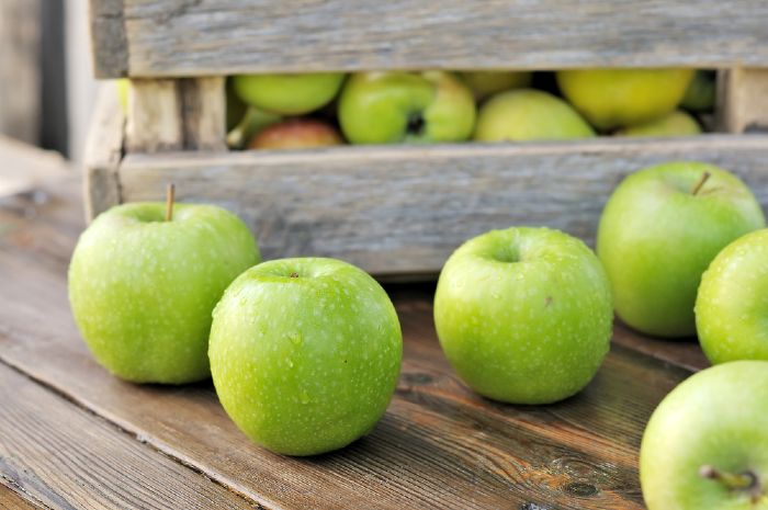 Green apples in wooden crate on wooden table