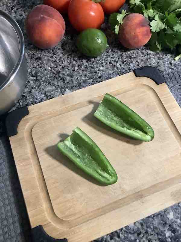 Jalapeno cut in half, seeded, and membranes removed on a wooden cutting board.
