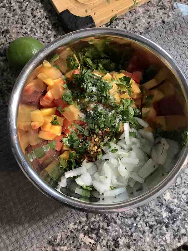 Chopped cilantro and onions on top of other peach salsa ingredients.