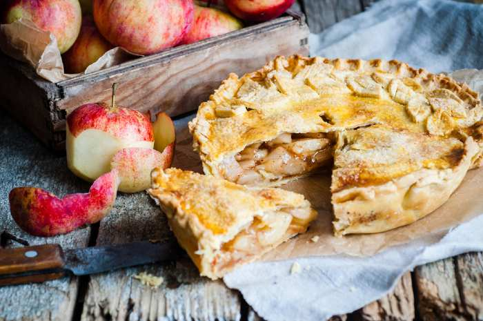Apple pie and apples on wooden table