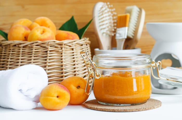 A glass jar of apricot face mask next to basket of whole apricots against a spa setting.  Improved skin health is among the many health benefits of apricots.