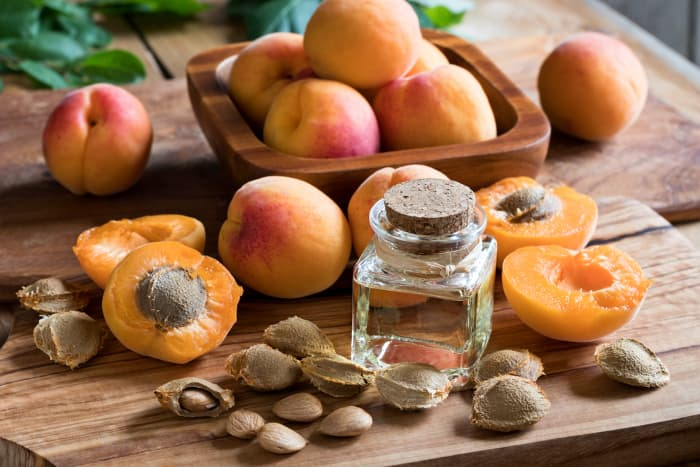 A bottle of apricot kernel oil among apricot halves, with whole apricots in the background.  Apricot nutrition even includes healthy skin.