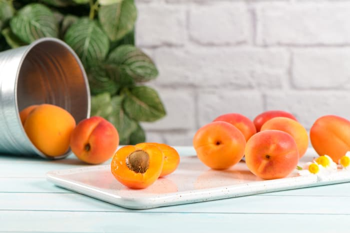 Apricots on a white cutting board.