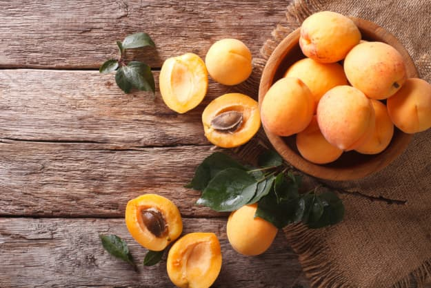 Overhead view of whole apricots in a wooden bowl and apricot halves next to it on a wooden table.