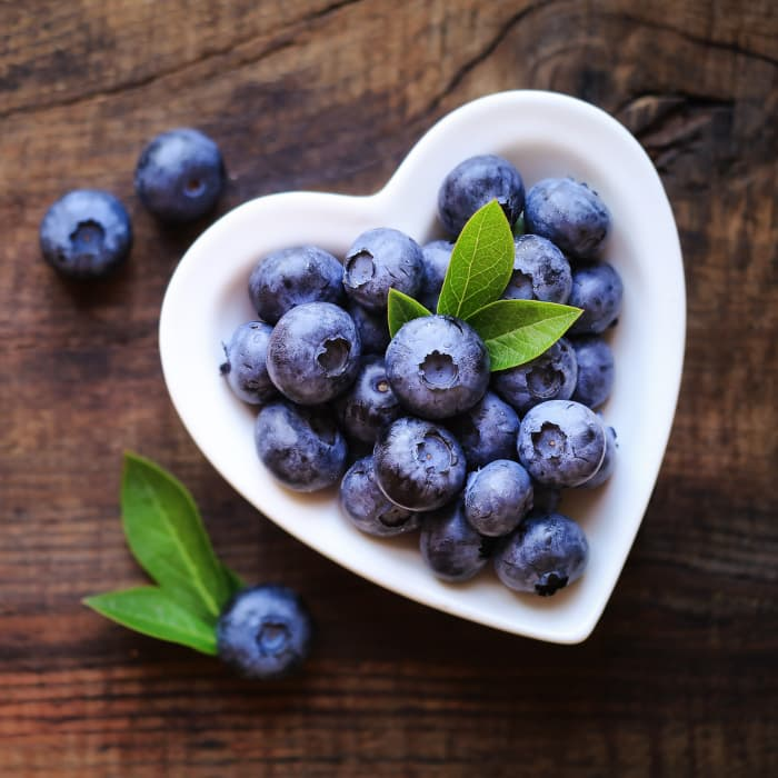 Overhead view of blueberries in a heart-shaped bowl.  A healthy heart is a benefit of blueberry nutrition.