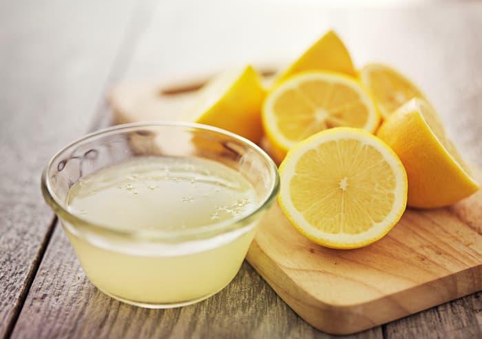 Bowl of lemon juice next to lemon halves on a cutting board.