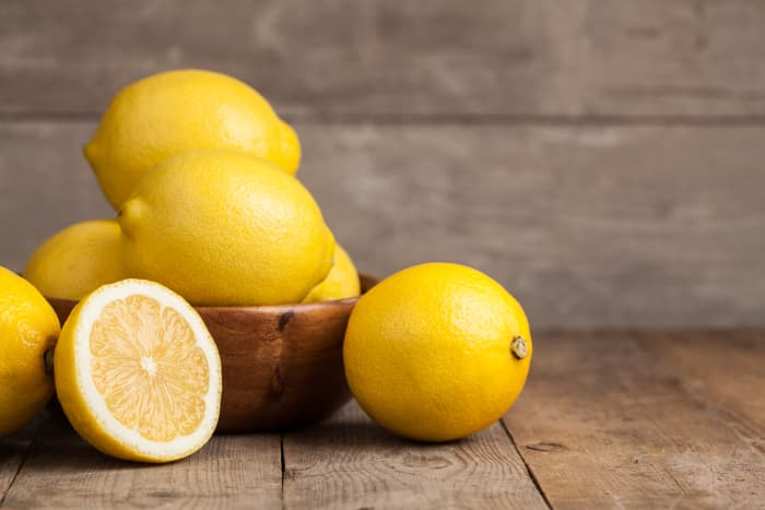 Bowl of whole lemons with a lemon half in the foreground.
