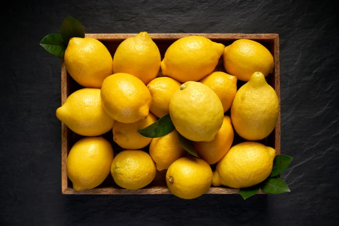 Overhead view of box of lemons on a dark surface.  Lemon nutrition isn't just limited to using lemon as a garnish for dishes -- eating this citrus fruit has many health benefits.
