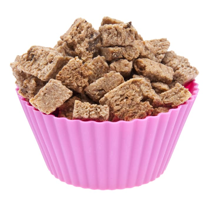 """A purple cupcake liner filled with cat treats.  Since the answer to """"Can cats eat cherries"""" is """"No.,"""" the good new is there are lots of cat treat recipes you can make with ingredients that are safe for cats to eat."""
