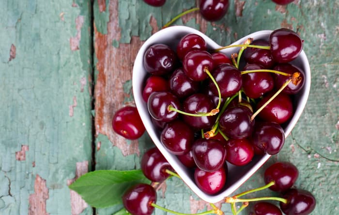 Overhead view of a heart-shaped bowl of fresh cherries.  Heart health if among the benefits of cherry nutrition.