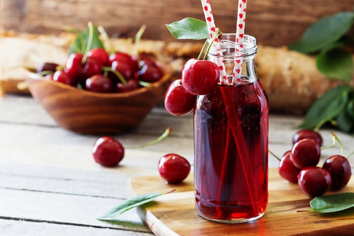 A bottle of cherry juice with straws, bowl of fresh cherries in the background.  Cherry nutrition isn't just about eating fresh cherries -- cherry juice has health benefits as well.