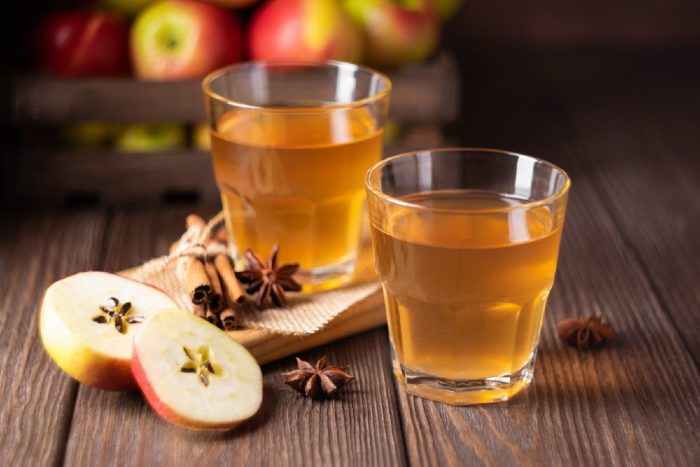 Hard cider on a wooden table at one of the best apple orchards in Minnesota