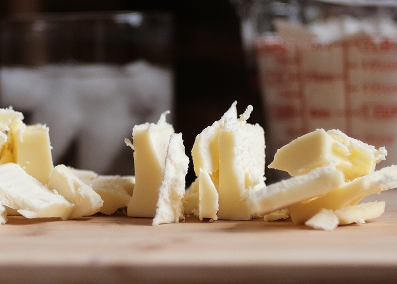 Cold butter cut into small pieces, glass measure of flour and glass of ice water in the background.