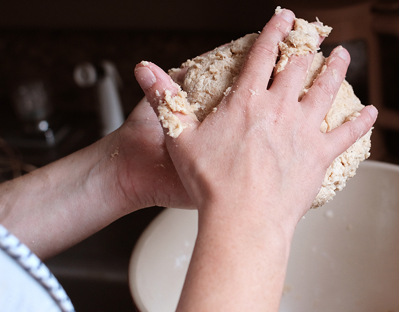 Woman's hands holding a ball of pie crust.