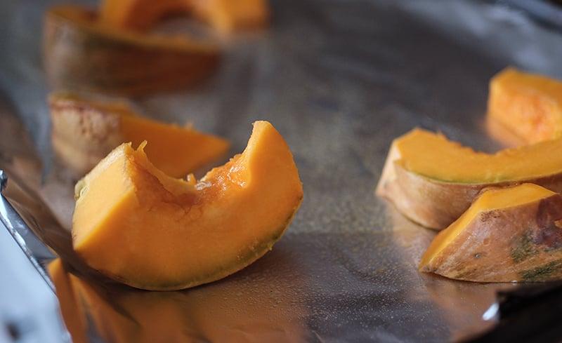 Pumpkin wedges on foil-covered baking sheet.
