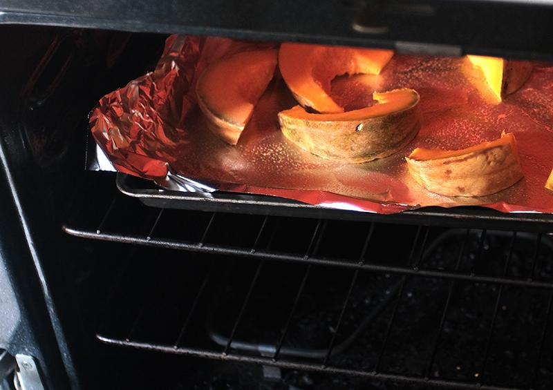 Baking sheet of pumpkin wedges in an oven.