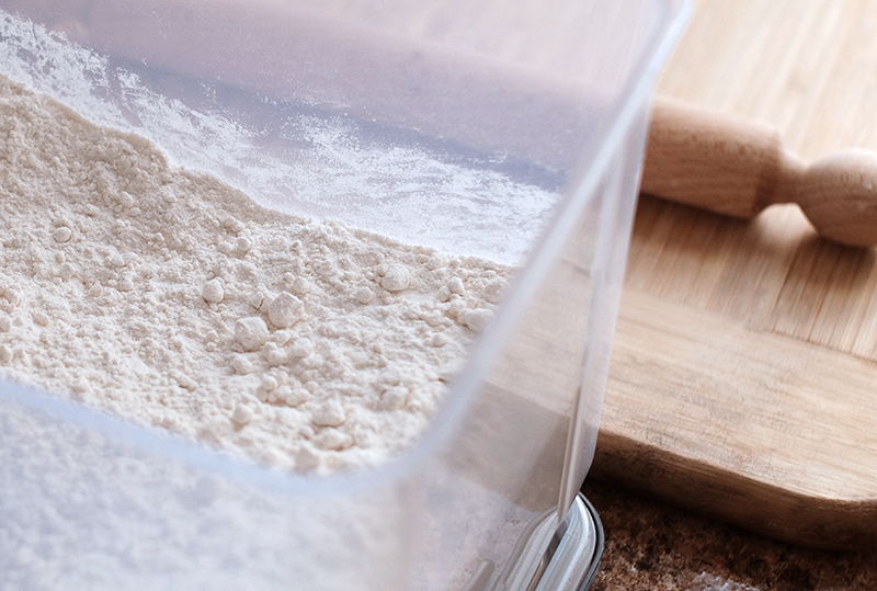 Container of flour, rolling pin and wooden board in the background.