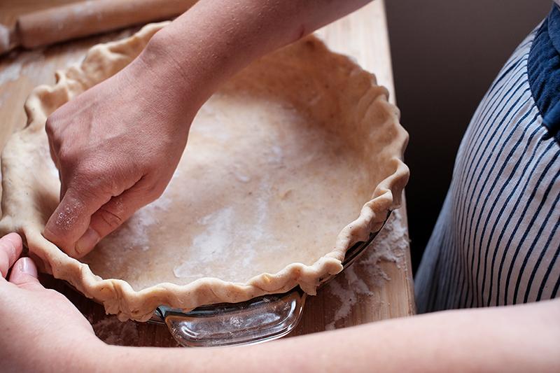 Woman's hands finger-crimping edges of pie crust.