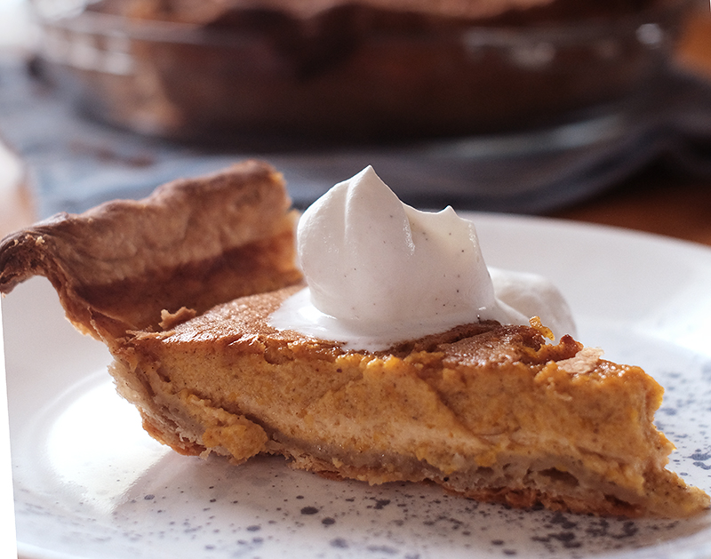 Closeup of a slice of pumpkin pie topped with spiced whipping cream.