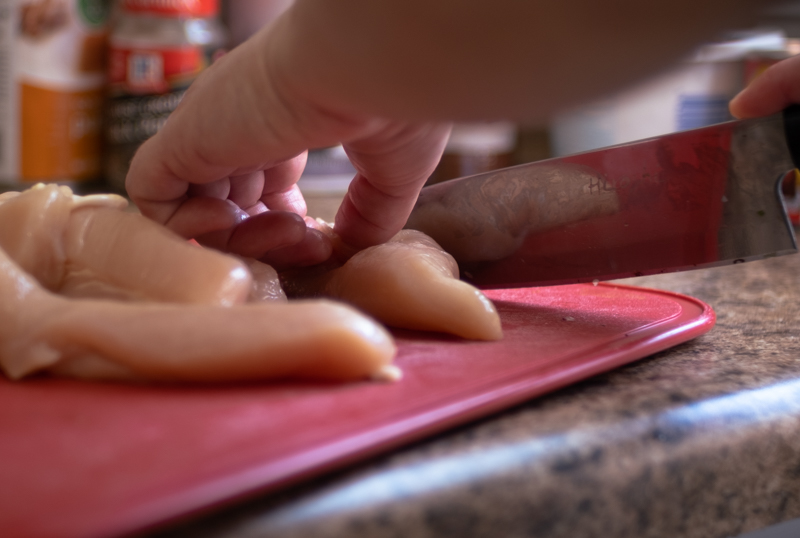 Closeup of hands using a chef's knife to cut raw chicken tenders.