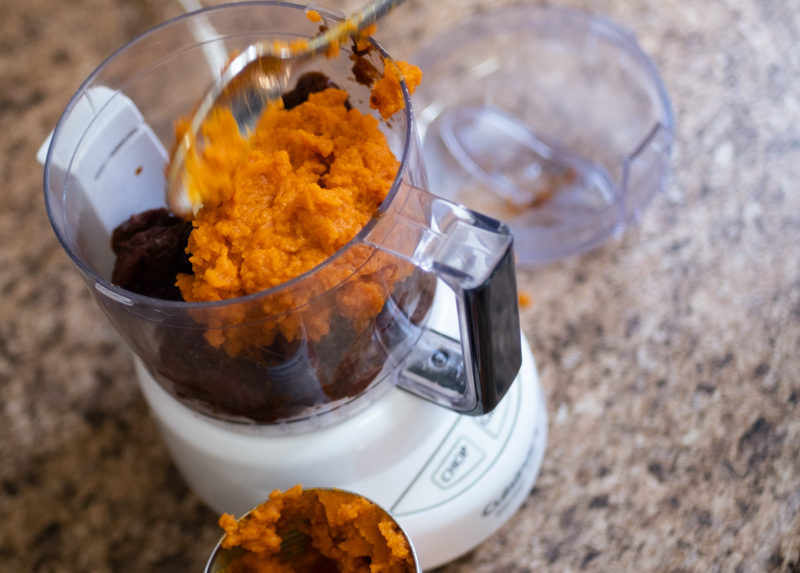 Overhead view of pumpkin puree being spooned into a food processor bowl.