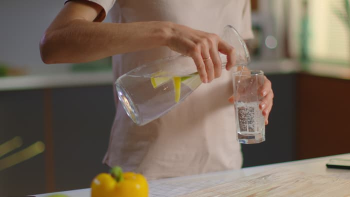 Woman pouring lemon water from a carafe into a glass.