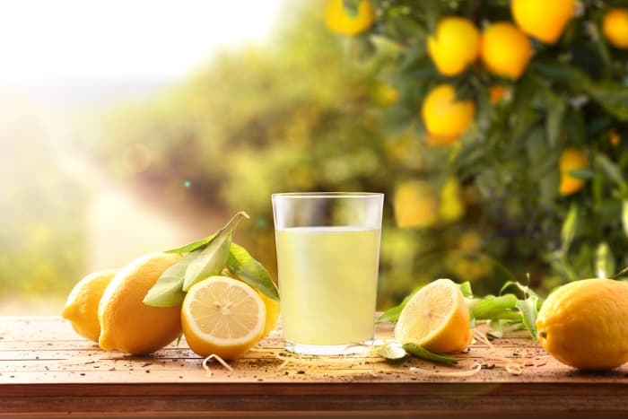 A glass of lemonade or lemon water with lemon halves and whole lemons around it.