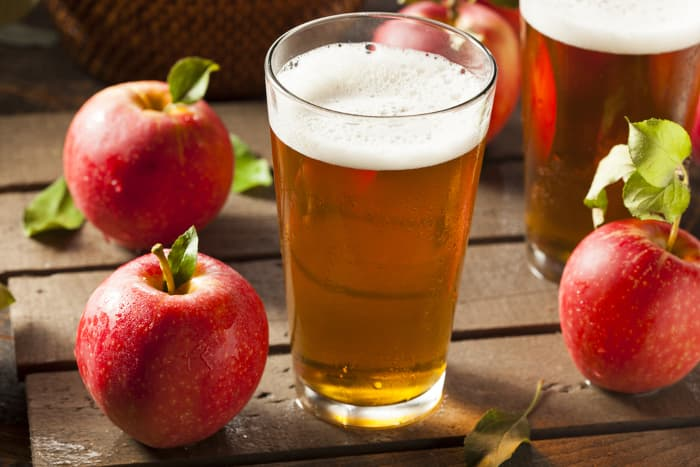 Pint glasses of hard cider surrounded by apples on a wooden table.  Aamodt's Apple Farm is the source of apples and the production site for Thor's Hard Cider.