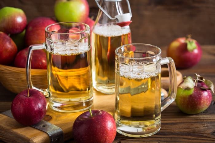 Two mugs of hard cider, bottle of hard cider and apples in the background.