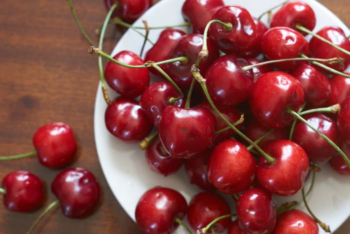 Closeup of plate of fresh cherries.  The health benefits of cherry nutrition are numerous,
