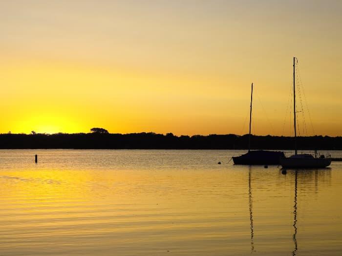 Two boats on White Bear Lake at sunrise.