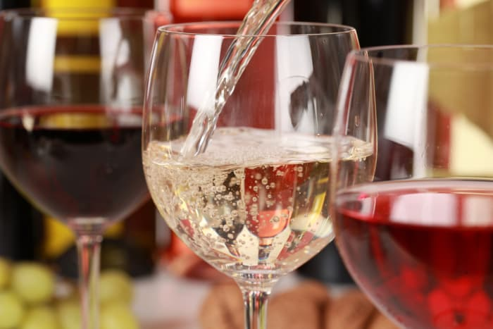 Closeup of three wine glasses with white wine being poured into the middle glass.  Wine tastings are available at St. Croix Vineyards, the on-site winery at Aamodt's Apple Farm.