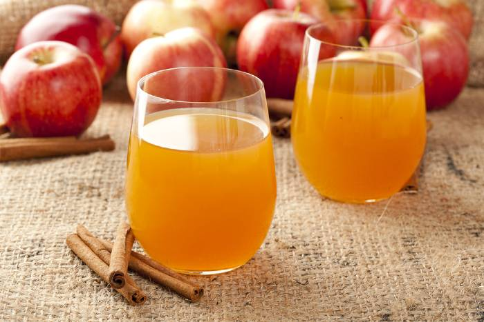Two glasses of cider and apples on burlap table cover.