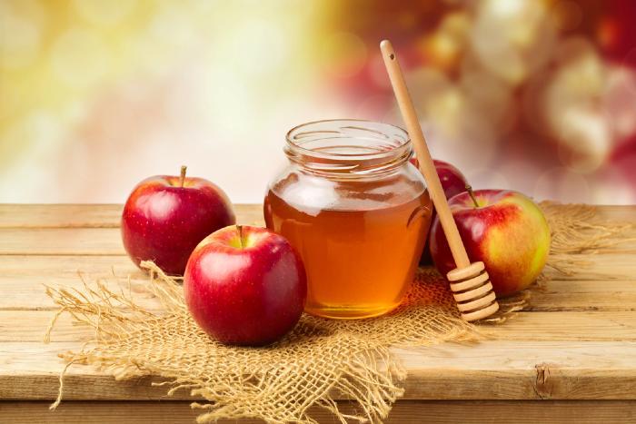 Honey jar and apples on wood table