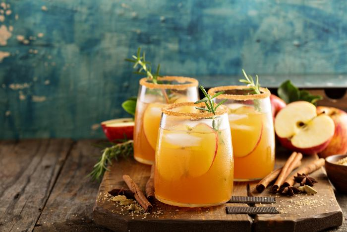 Apple cider drinks on wooden board with sliced apples