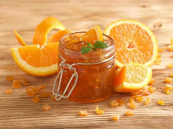 Orange marmalade and oranges on a wooden table.