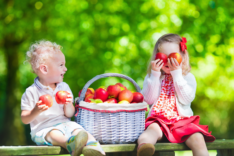 Two children playing with a bushel of apples.