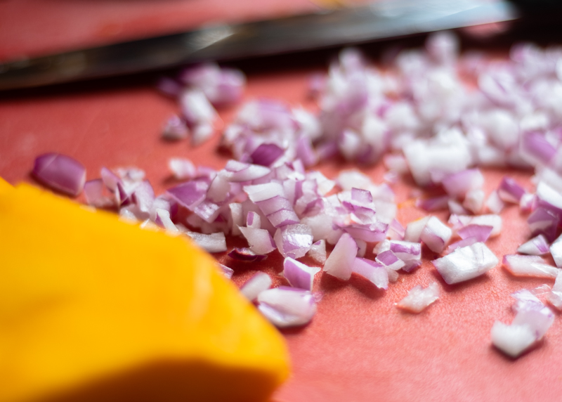 Closeup of chopped purple onion on a red cutting board.