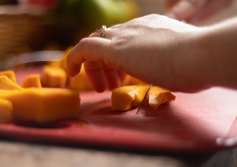 Hands chopping pumpkin into one-inch pieces on a red cutting board.